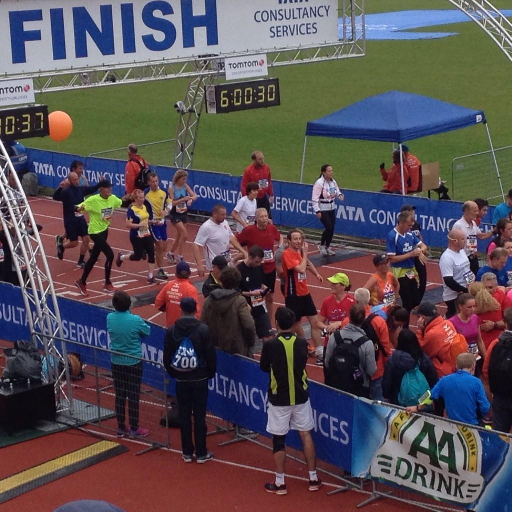 In het geel met zwarte pet over de finish van de halve marathon 2015 in het Olympisch Stadion Amsterdam.