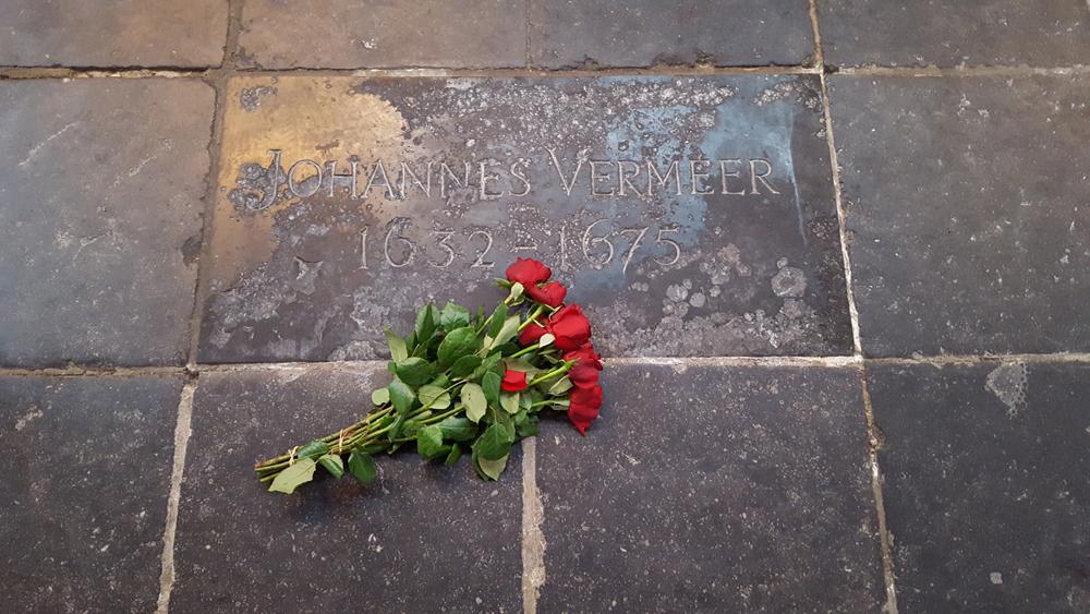 Rode rozen op de steen die de vermoedelijke locatie van het graf van Johannes Vermeer markeert.